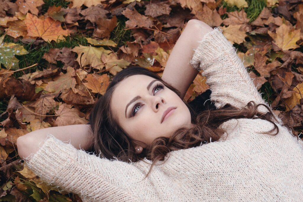 Kvinde ligger på en bunke blade