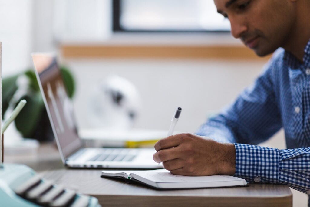 Mand med computer der skriver